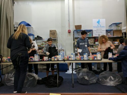 Volunteers on the assembly line placing items of food into the backpacks.